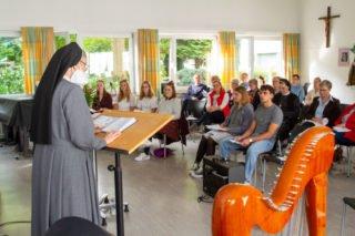Schwester Laetitia Müller eröffnet die Aussendungsfeier in der Musikaula des Berufskollegs Bergkloster Bestwig. Foto: SMMP/Ulrich Bock